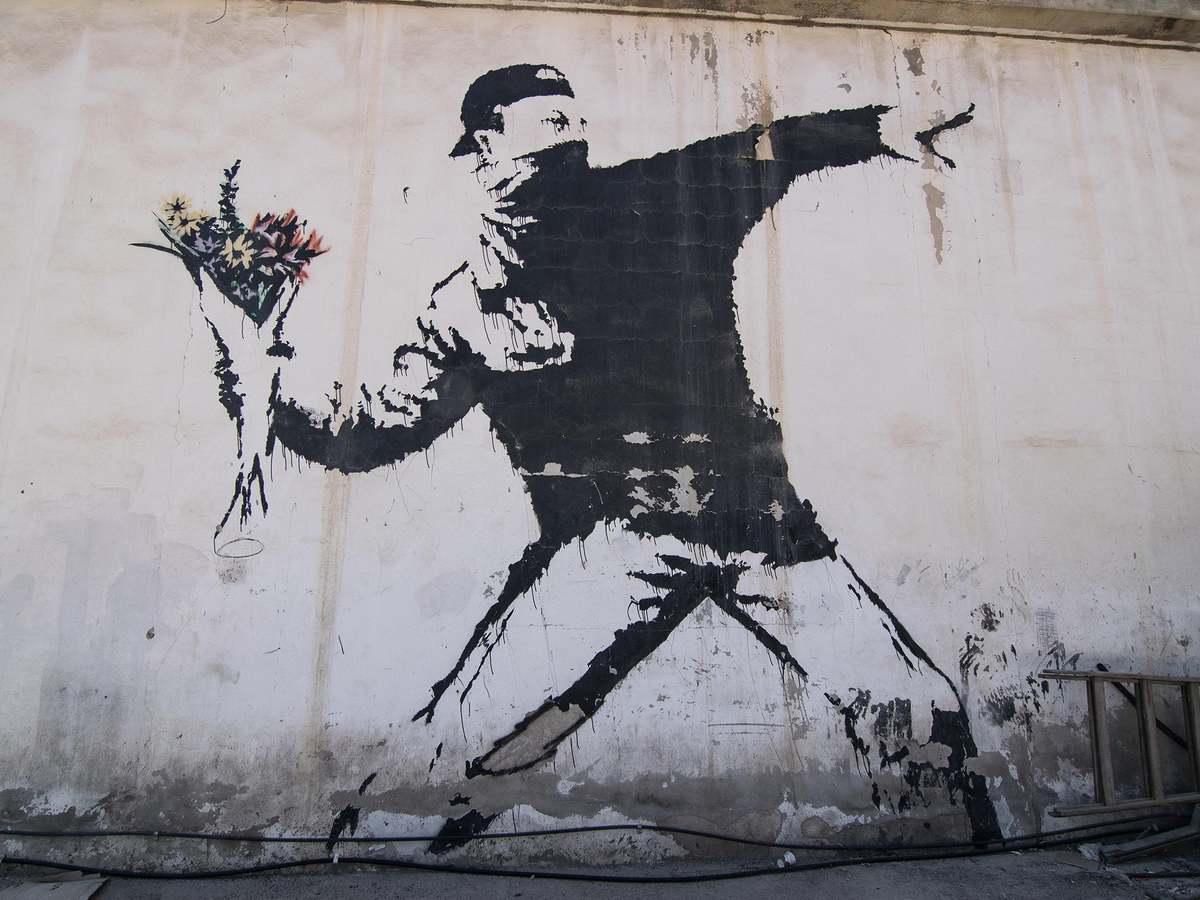 """EUIPO recusa a Banksy o reconhecimento do direito ao registo de marca sobre a icónica obra """"The Flower Thrower"""" por se recusar a revelar a identidade em Tribunal."""